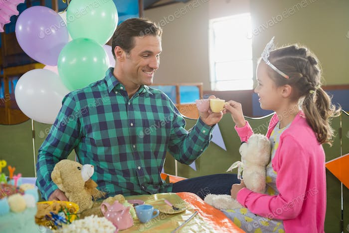 Father and girl toasting their tea cups while playing with toy kitchen set