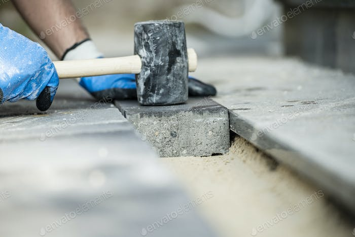 Builder laying a paving stone or brick