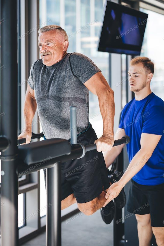 Gym instructor helping senior man at the gym.