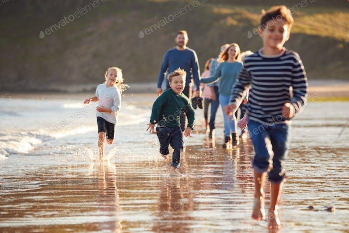 Kinder laufen voraus als Multi-Generation Familienspaziergang entlang der Küste am Winter Beach Urlaub
