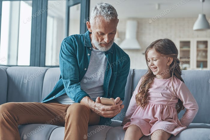 Cute little girl using smart phone while spending time with grandfather and at home