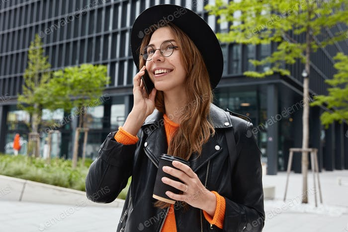 Street style concept. Satisfied female walks around city, has phone conversation, holds takeaway cof