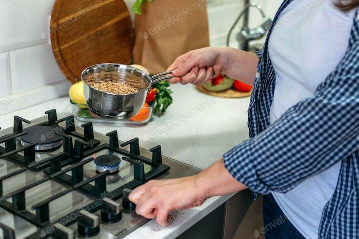 Frau kocht Ancient Grains Porridge. Erbe des Erbstück Alte Körner auf der Küche zu Hause.  Gesundheit