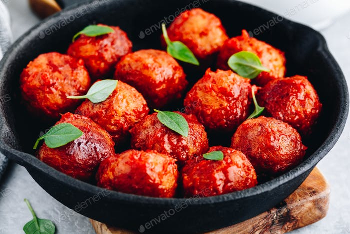 Homemade beef or chicken meatballs in tomato sauce in a frying pan