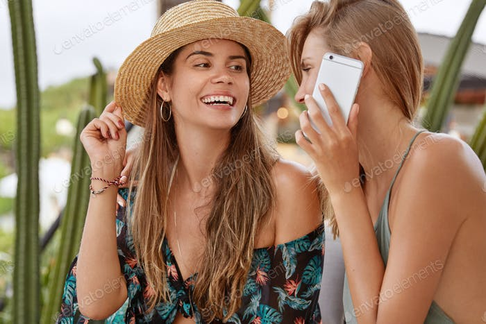Friendship, leisure and technology concept. Attractive European female in straw hat looks happily at