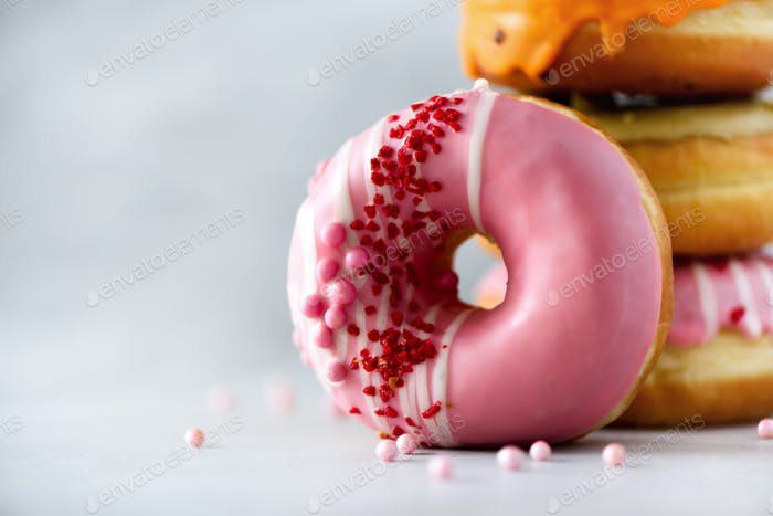 Stack of glazed colorful assorted donuts with sprinkles on grey cement background. Copy space. Sweet