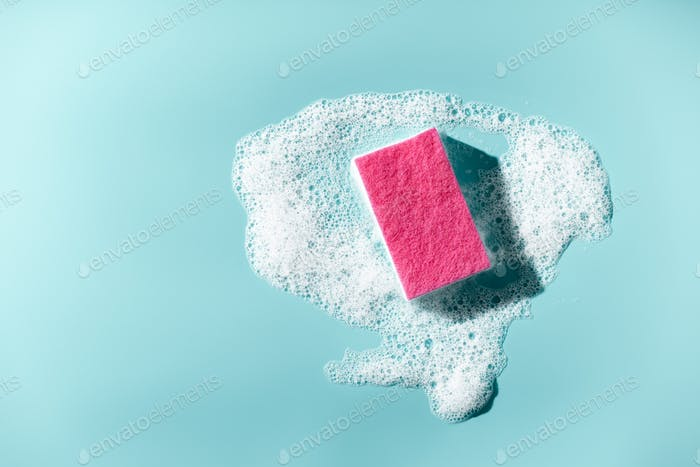 Cleaning sponge and a soapy foam on a blue background. Cleaning concept, cleaning service