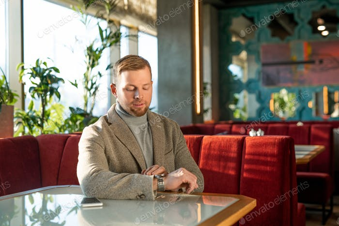 Elegant man looking at wristwatch while sitting by table on soft velvet couch