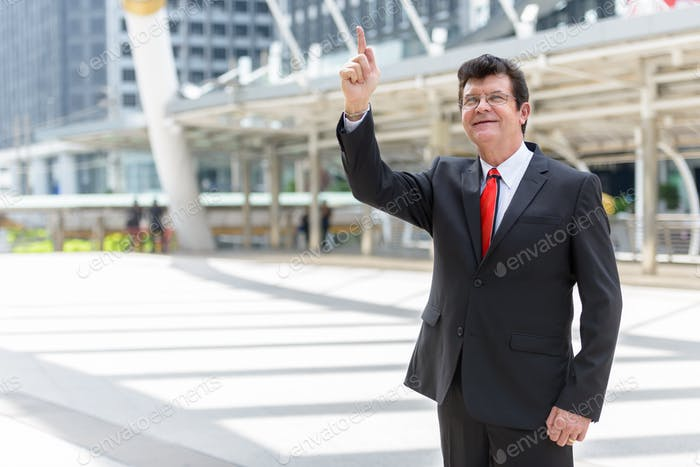 Mature happy businessman pointing finger up in front of modern building at Bangkok city