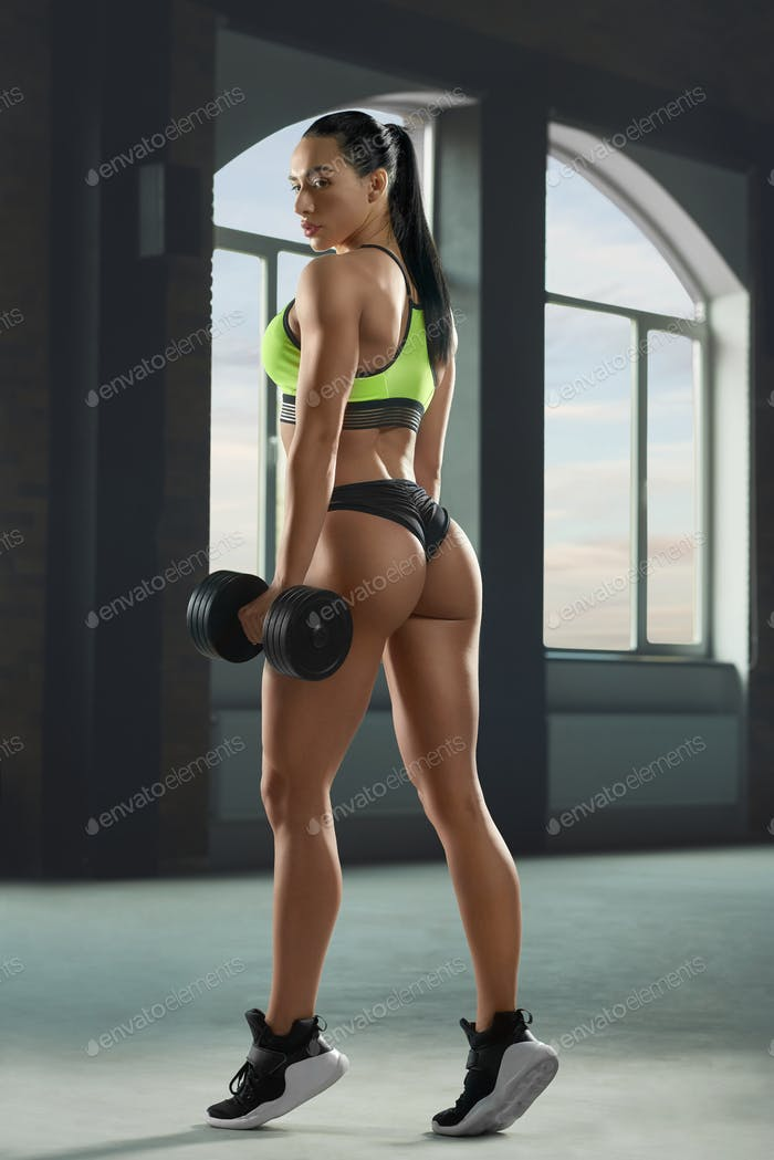 Photo of sexy athletic sporty woman posing with dumbbells