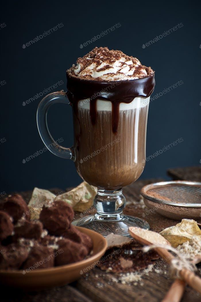Kaffee mit Sahne und schlampigen Krümel auf einem alten Holztisch.