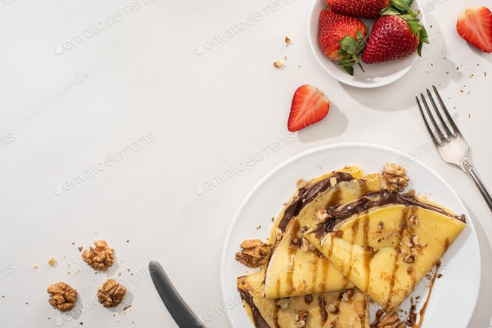 Tasty Crepes With Chocolate Spread And Walnuts on Plate Near Bowl With Strawberries And Cutlery