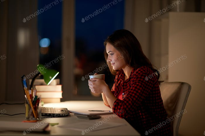 student woman with laptop and coffee at night home