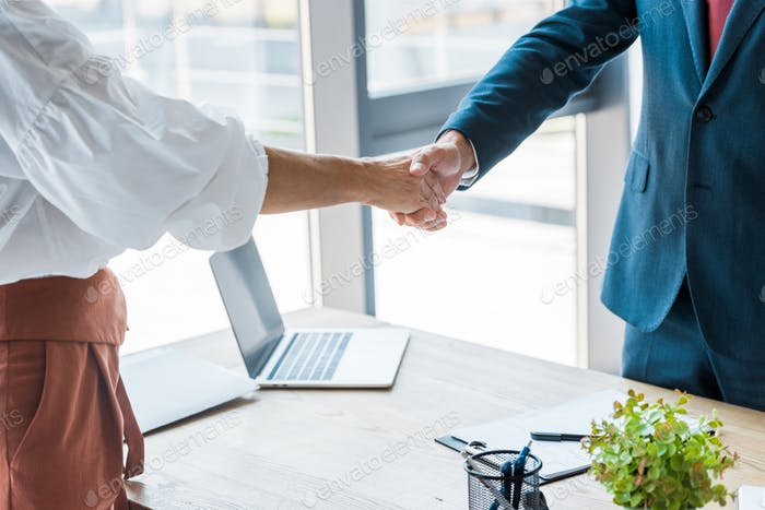 cropped view of employee and recruiter shaking hands in office