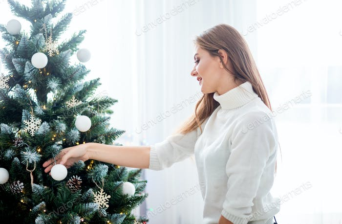 Young woman decorate the Christmas tree in bright white room