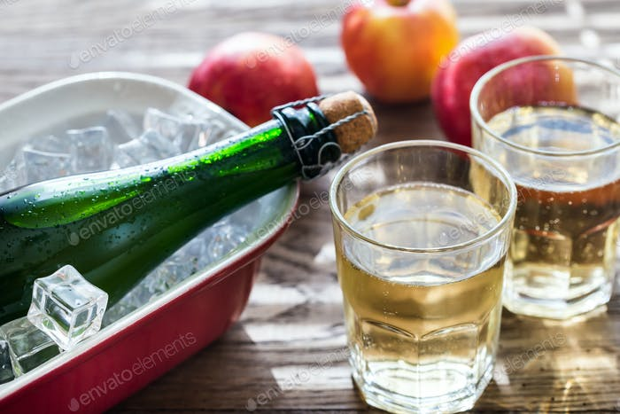 Bottle and two glasses of cider on the wooden background