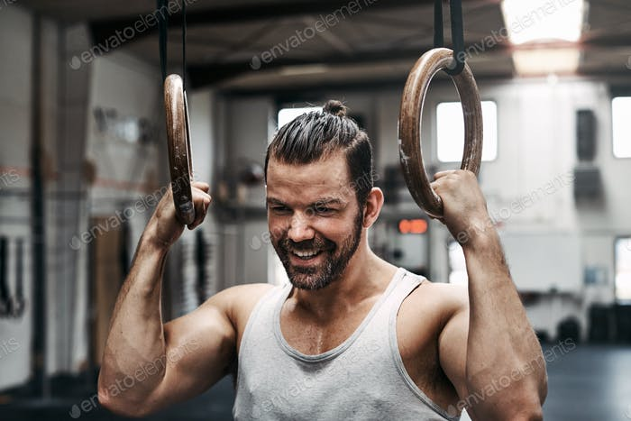 Fit man smiling while exercising with rings at the gym