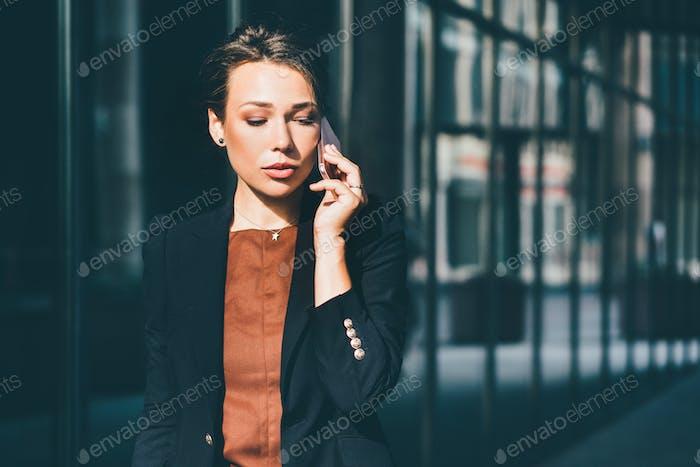 Geschäftsfrau im Gespräch auf Handy im Stadtbild Hintergrund.
