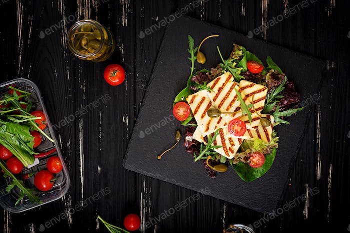 Fresh salad with grilled cheese, tomatoes, capers, lettuce and arugula. Flat lay. Top view