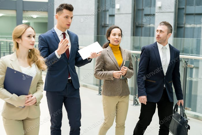 Confident manager guiding tour for business partners