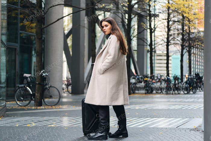 Attractive stylish girl in coat confidently looking aside standing on city street with suitcase