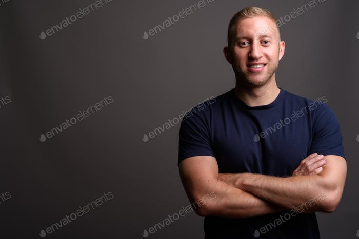 Man with blond hair against gray background