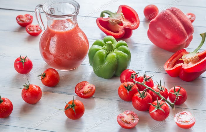 Fresh tomatoes, peppers and jug of juice