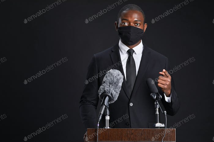 Official Speaking to Microphone Wearing Mask