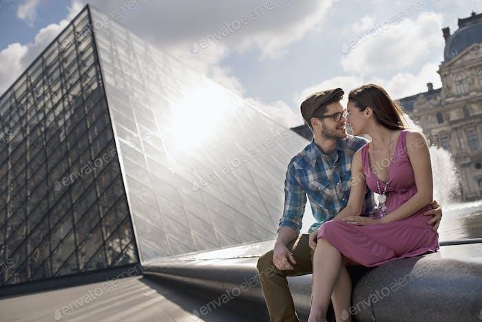 Ein Paar sitzt am Brunnen am gläsernen Eingang zum Louvre, Paris.