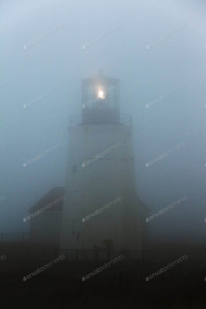 Ghostly lighthouse beacon in thick fog NL Canada