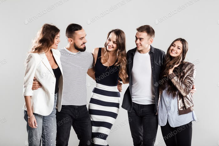 Company of friends in fashionable casual clothes stand together and talk on a white background in