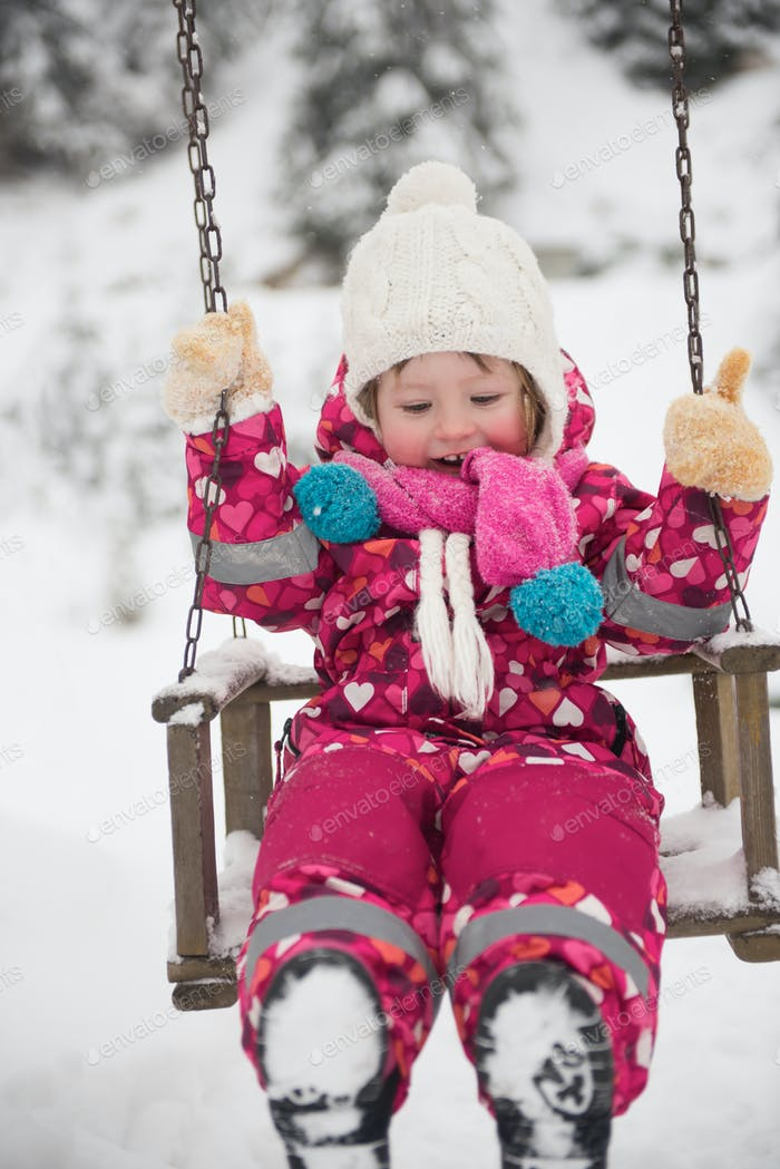little girl at snowy winter day swing in park