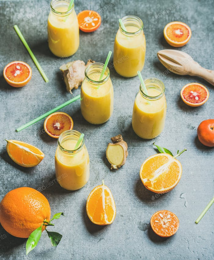 Healthy yellow smoothie with ginger in bottles over grey background