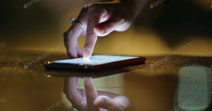 Toque con el dedo en el teléfono móvil por la noche
