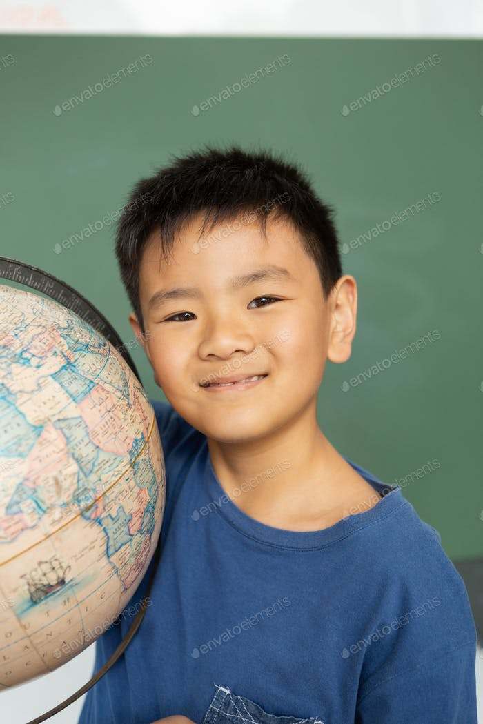 Asian schoolboy with globe standing against green chalkboard in a classroom