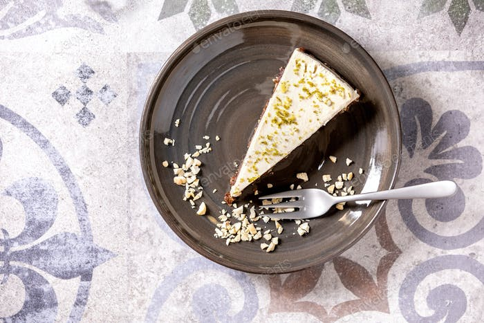 Raw vegan cheesecake with lime zest and cashew nuts on plate. Top view