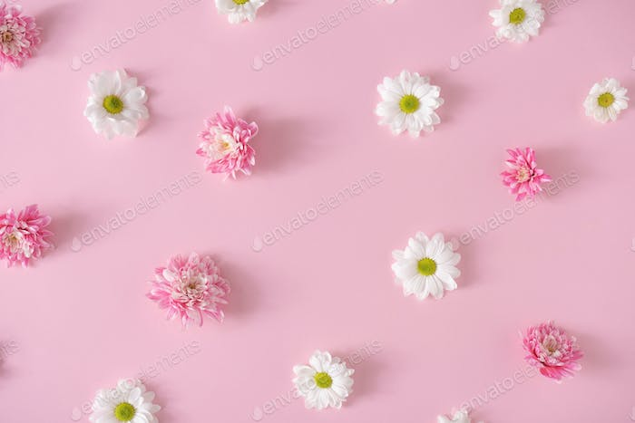 Creative pattern made with pink and white flowers on pastel pink background.