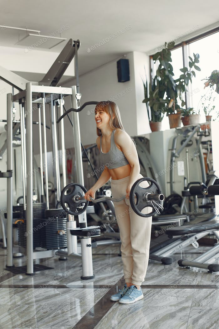 A beautiful girl is engaged in a gym with a barbell
