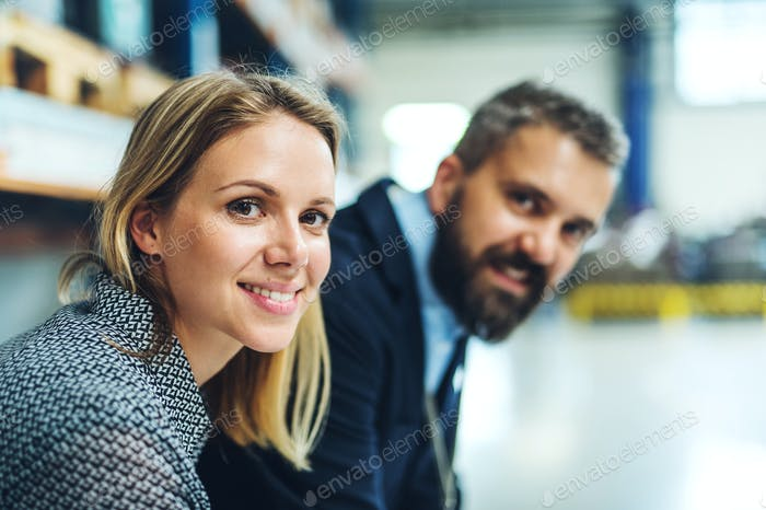 A portrait of an industrial man and woman engineer in a factory, looking at camera.