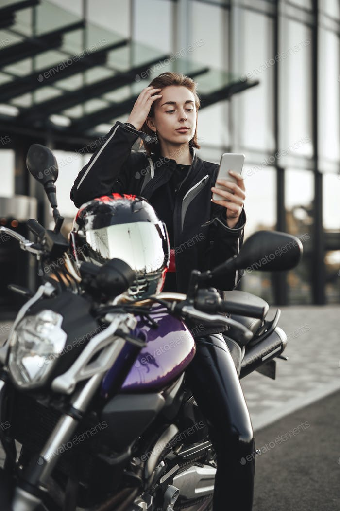 Beauty in a motorcycle jacket sits on a purple motorbike and looks at her phone