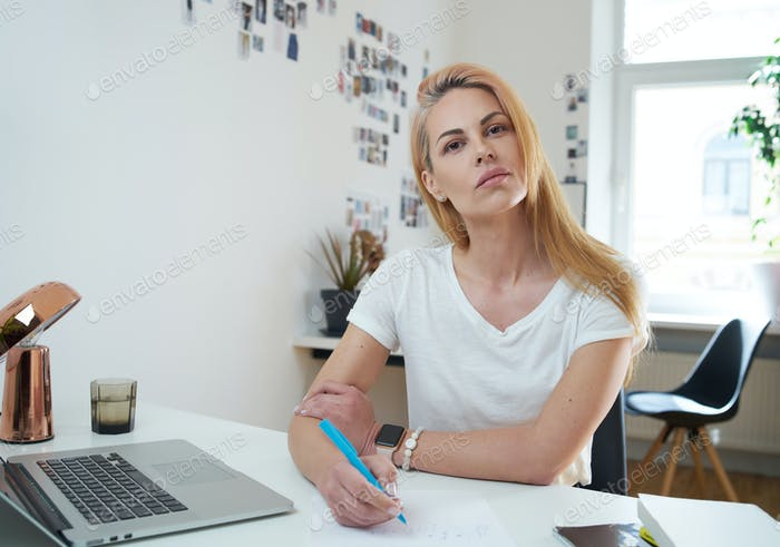 Caucasian secretary looks at camera with serious face in modern office