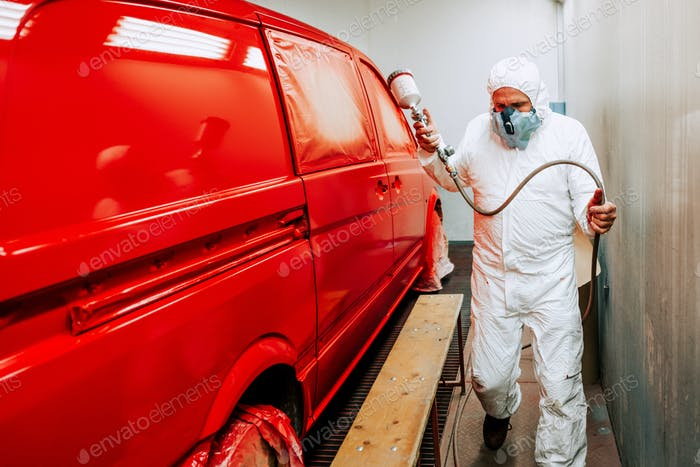 Portrait of auto mechanic worker painting a red van, car