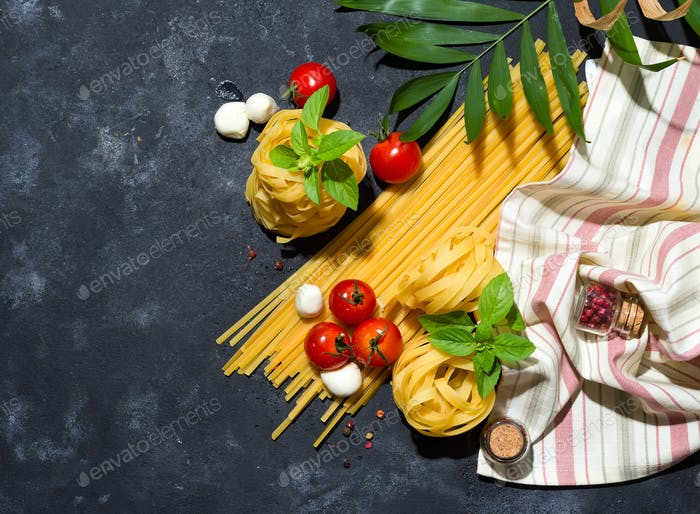 Fettuccine and spaghetti with ingredients for cooking pasta on black stone slate background