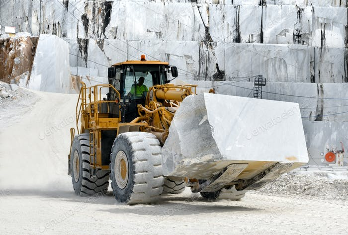 Heavy duty front end loader moving marble