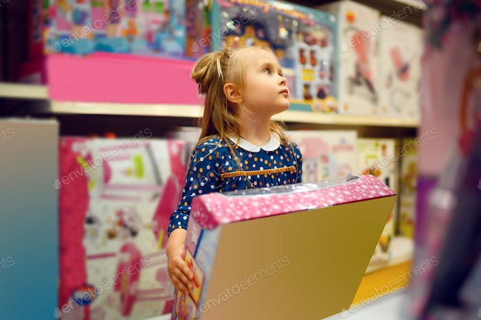 Little girl holds box with doll in toy store