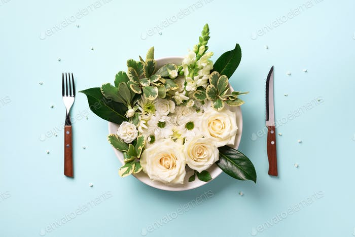 White flowers on plate, fork, knife over pastel blue background. Healthy eating, vegan diet concept