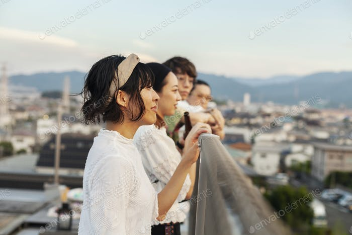 Group of young Japanese men and women standing on a rooftop in an urban setting.