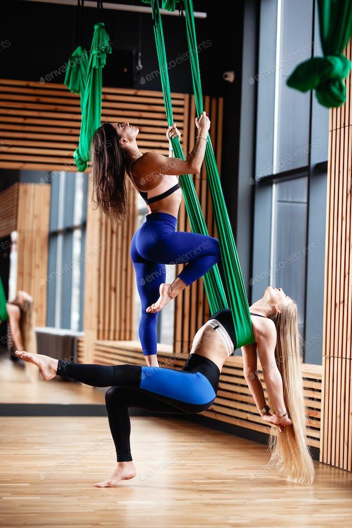 Zwei junge athletische Mädchen Brünette und Blondine tun Fitness auf der grünen Luftseide in der