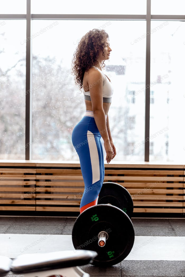 Slim curly dark-haired girl dressed in sports clothes is doing back squats with heavy barbell in the