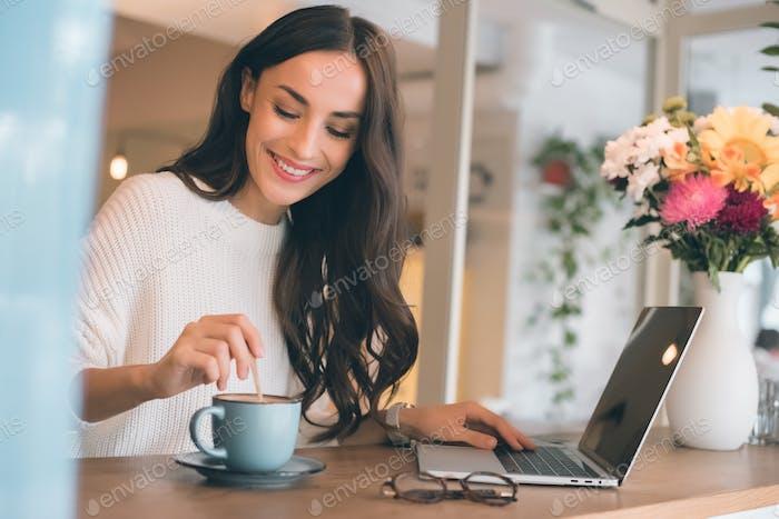 lächelnde Freiberuflerin sitzt mit Laptop und Kaffeetasse am Tisch im Café